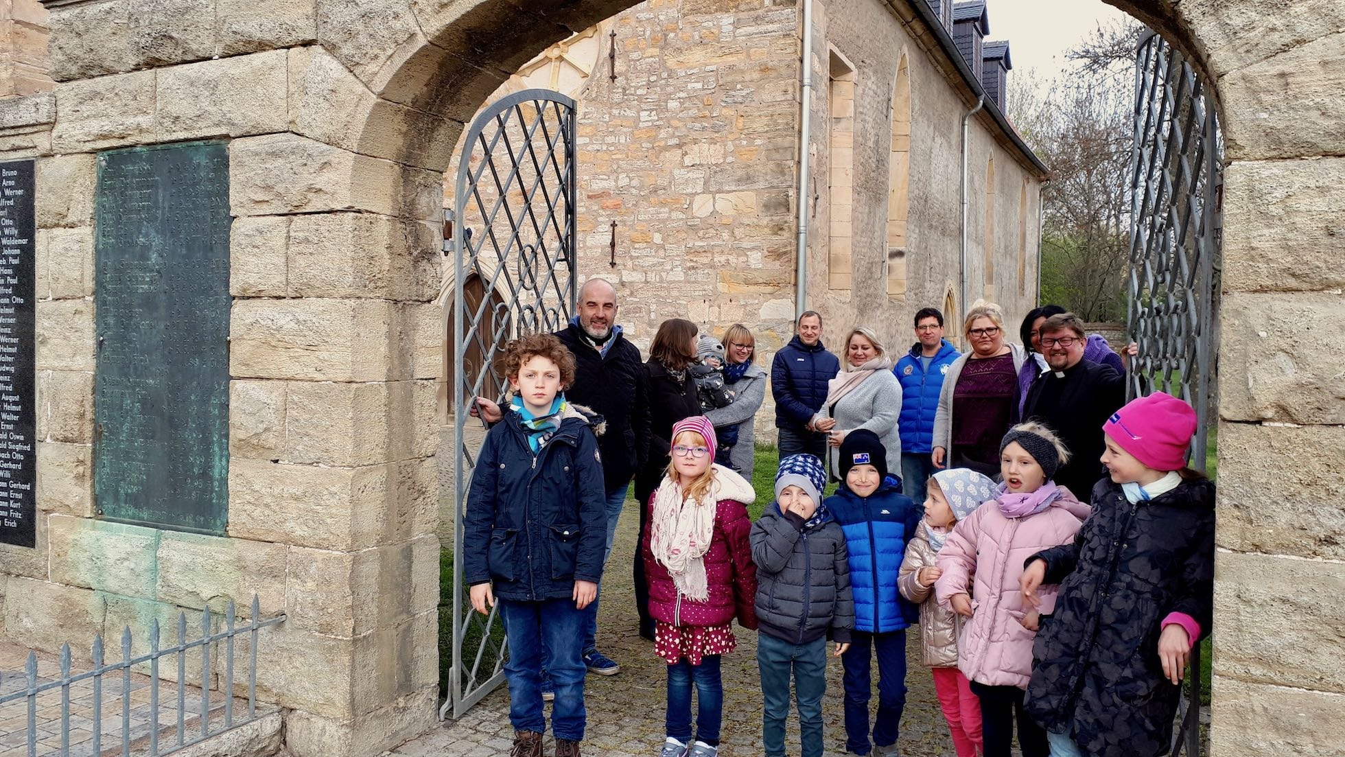 Gruppe von Erwachsenen und Kindern stehen im Kirchentor der Kirche von Elxleben zum Familienkirchentag 2019