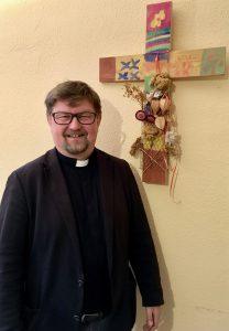 Bild des Pfarrers Olaf Meyer vor einem künstlerisch gestaltetem Kreuz