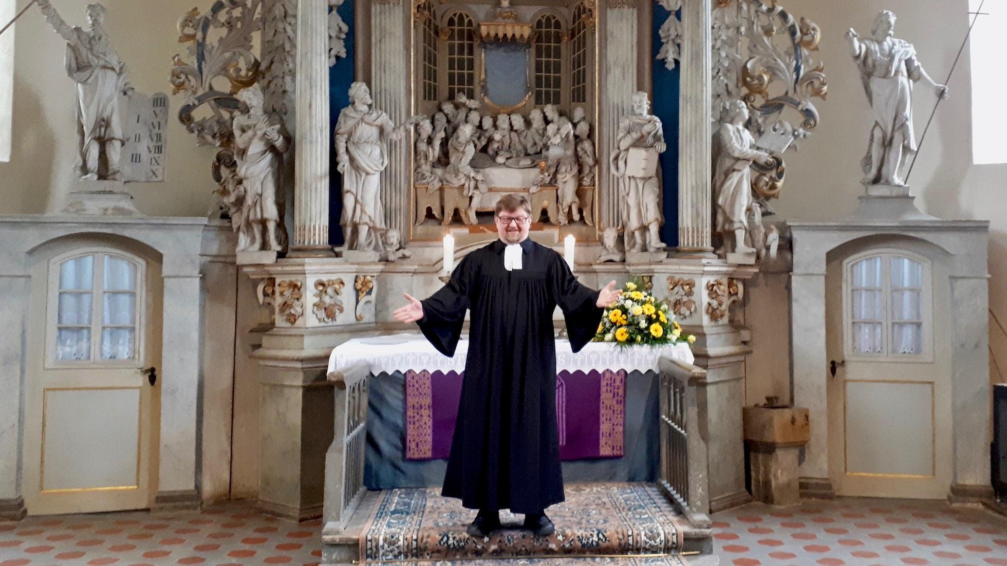 Pfarrer Olaf Meyer steht mit ausgebreiteten Armen vor dem Altar der Kirche in Elxleben